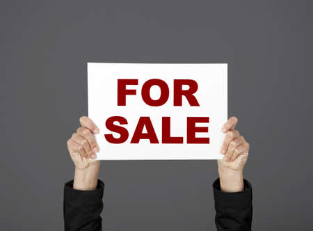 Woman holding a billboard with the text For Sale photo