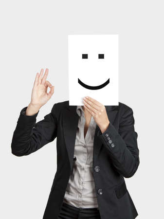 Woman showing a happy emoticon in front of face and making a okay gesture with the right hand  photo