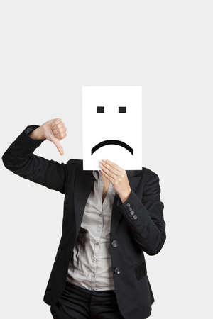Woman showing a sad emoticon in front of face and making a thumbs down gesture with the right hand  photo