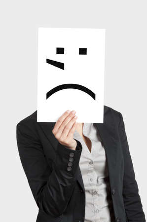 Woman showing a blank paper with a crying emoticon in front of her face photo