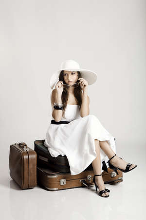 Fashion woman sitting over her luggage and waiting, isolated on a grey background photo