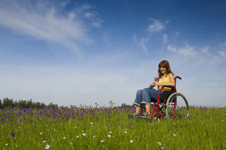 Happy handicapped woman on a wheelchair over a green meadow  photo