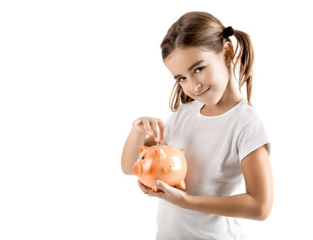 economizing: Little girl holding a piggy-bank and inserting a one euro coin