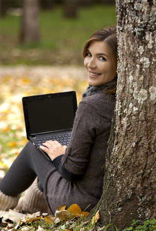 Beautiful woman working with a laptop in outdoor photo