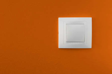 switch on the light: Simple interruptor de la luz en una pared de color naranja Foto de archivo