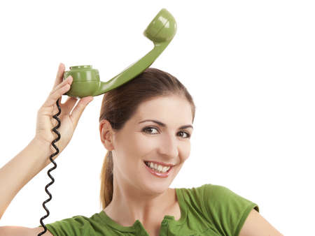 Beautiful woman doing funny faces with a vintage green telephone Stock Photo - 11278928