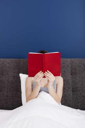 mujer leyendo libro: Mujer leyendo un libro con el rostro cubierto por el libro