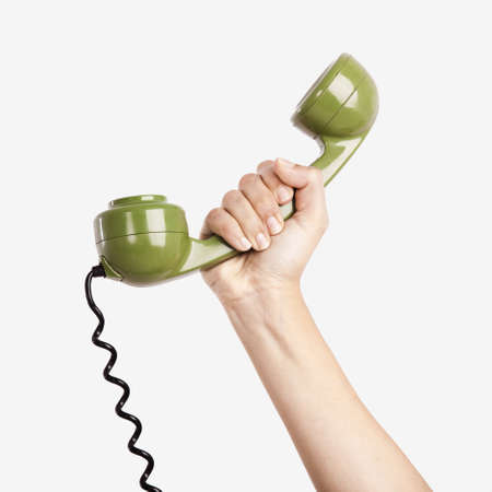 phone cord: Female hand holding a green handpiece from a vintage telephone