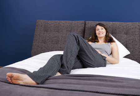 Beautiful happy young woman in pajama and lying on the bed photo