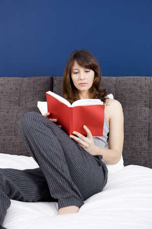 Beautiful young woman  on the bed  reading a book photo