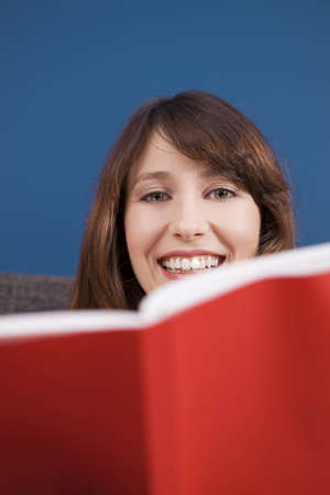 Beautiful and happy young woman reading a book photo
