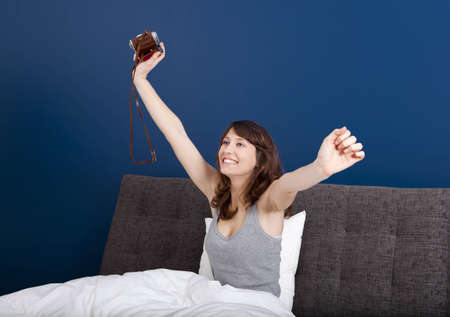 Young girl on the bed holding a photographic camara Stock Photo - 11622312