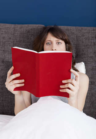 terrified: Beautiful young woman reading a book with a astonish expression Stock Photo