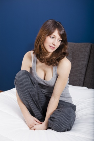siting: Beautiful young woman in pajama and sitting on the bed