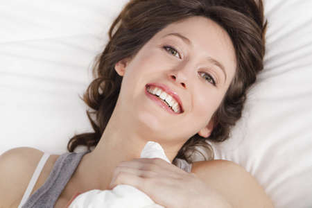 Beautiful and natural young girl on the bed laughing  photo