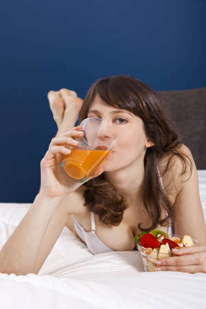 Beautiful young woman eating the breakfast on the bed photo