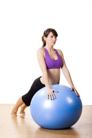 Schöne junge und sportliche Frau, die Übungen auf einem Fitness-Ball