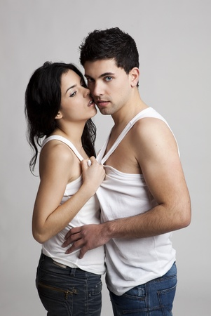 Sexy young couple isolated on a gray background photo