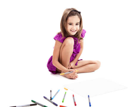 Girl sitting on floor and making drawings on paper