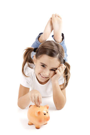 economizing: Little girl lying on floor and inserting a one euro coin on the piggy-bank Stock Photo