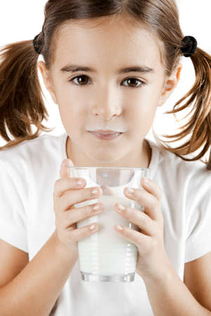 Little girl with a milk moustache after drink a cup of milk photo