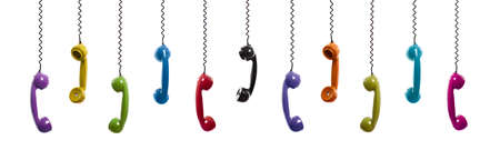 Multi colored handset pieces suspended by the phone cord, isolated on white background photo