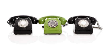 old phone: Green phone in the midle of two black phones, isolated on white background