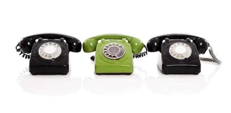 telefono antico: Telefono verde nel midle di due telefoni neri, isolato su sfondo bianco