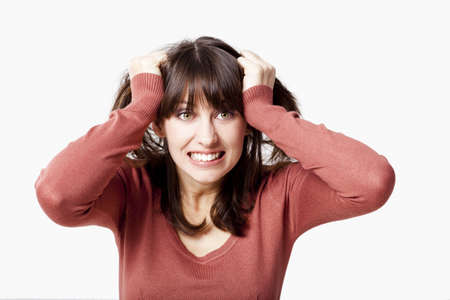 pulling hair: Portrait of a stressed young woman pulling her hair out, isolated over a gray background Stock Photo