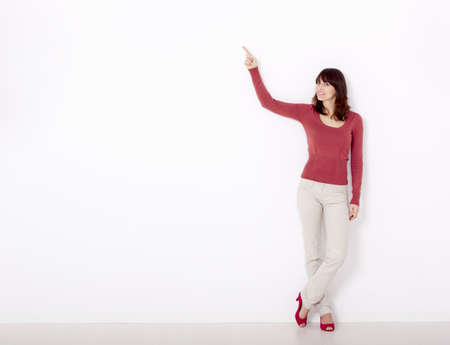 Beautiful young woman pointing to the right side with copyspace, against a white wall photo