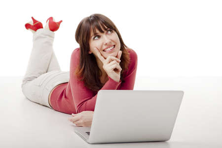 Beautiful woman lying on the floor and thinking while working on a laptop photo