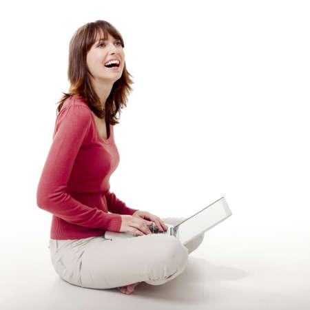 mujer sentada: Hermosa mujer sentada en el suelo de la risa y el trabajo con un ordenador portátil