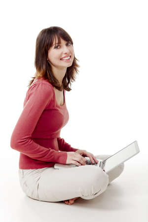 Beautiful woman sitting on the floor laughing  and working with a laptop photo