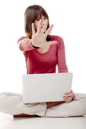 frau sitzt am boden: Sch�ne Frau mit einem Laptop, auf dem Boden sitzend mit einer Hand vor dem Gesicht