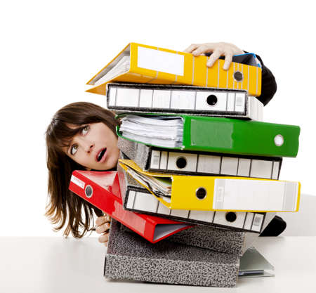 Business woman in the office embracing a pile of folders, isolated on white background Stock Photo