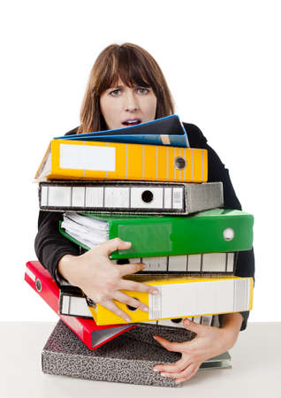 Business woman in the office embracing a pile of folders, isolated on white background photo