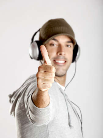 Portrait of a happy young man showing thumbs up and listen music with headphones photo