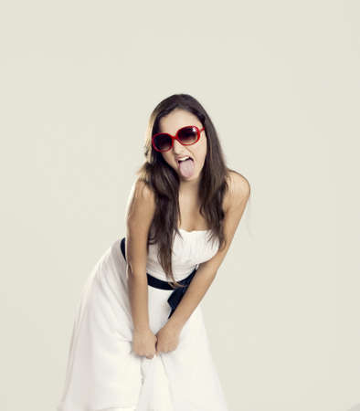 Beautiful young woman with a white dress and sunglasses showing her tongue out photo