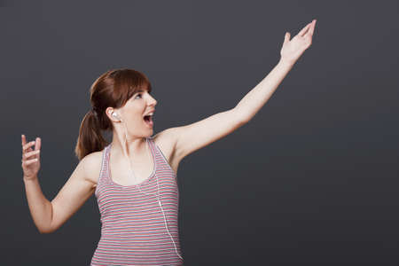 Happy young woman dancing and singing while listen music Stock Photo - 12165325