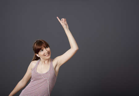 Happy young woman dancing and singing while listen music Stock Photo - 12165300