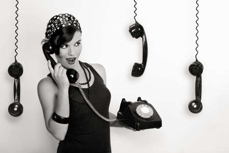 Beautiful and fashion young woman with a pin-up look. posing with a vintage phone photo