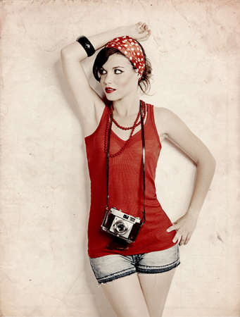 pin up: Portrait of a beautiful and fashion young woman with a photographic camera Stock Photo