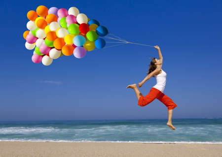 Bella joven y atlético, con globos de colores que saltan en la playa