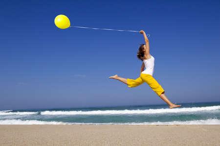 personas saltando: Chica hermosa y atlética saltar con un balón en la playa
