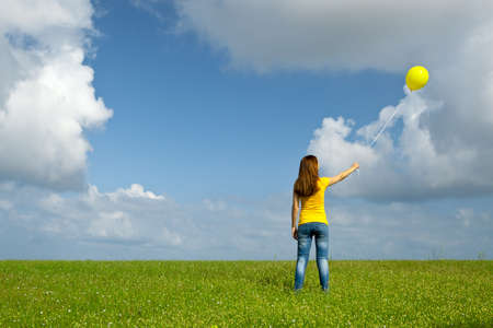 flying woman: Happy young woman with a yellow balloon on a green meadow