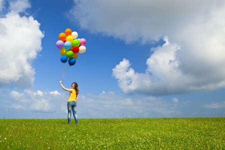 Happy young woman with colorful balloons on a green meadow photo