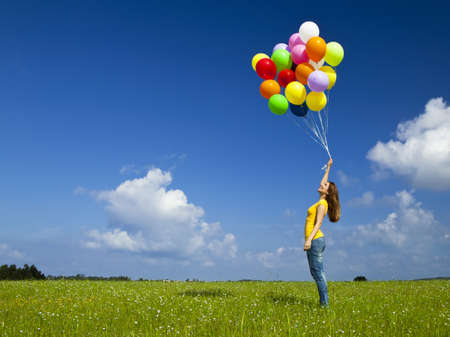 balloons  green: Happy young woman with colorful balloons on a green meadow