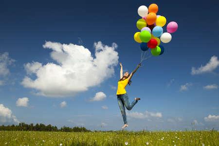 カラフルな風船を保持している、緑の牧草地の上を飛んで幸せの若い女性