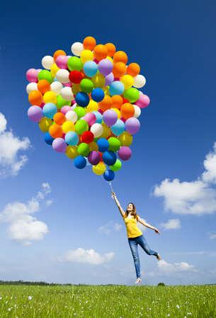 volar: Mujer joven feliz celebración de coloridos globos y volar sobre un prado verde