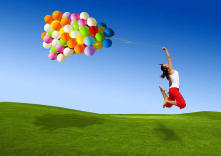 weather balloon: Beautiful and athletic Girl jumping with balloons on a green meadow